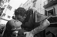 Storico Carnevale di Ivrea, Battaglia delle Arance. Un lanciatore bacia la sua ragazza dal carro dopo una battaglia --- Historic Carnival of Ivrea, Battle of the Oranges. A thrower kissing his girl from the wagon after a battle