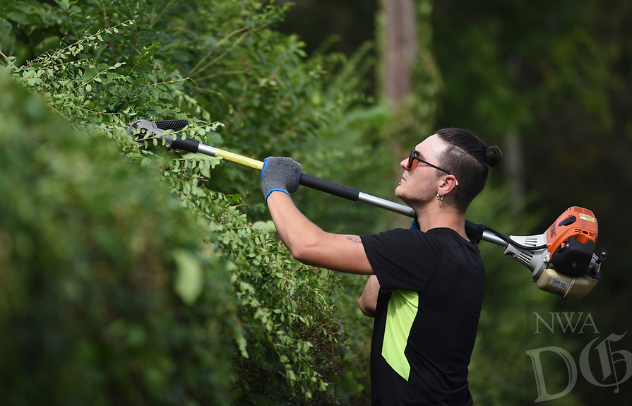 NWA Democrat-Gazette/DAVID GOTTSCHALK Tyler Hunter trims Friday, August 9, 2019, the perimeter bushes at Calvary Baptist Church on No. Porter Road in Fayetteville. Hunter was working with Kendall Prater, with the church, and staff for the job that also included mowing.