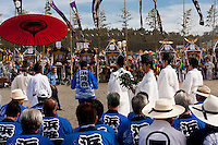 Shinto priests carry-out a ceremony to bless the mikoshi during the Hamaorisai Matsuri that takes place on Southern Beach in Chigasaki, near Tokyo, Kanagawa, Japan Monday July 18th 2011. The festivals marks the celebration of Marine Day and the rescuing of a divine image that was washed ashore in the area. Over thirty Mikoshi or portable shrines are carried through the night from surrounding shrines to arrive on the beach for sunrise. There they are blessed and then carried into the surf to purify them.