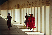 Pagan, Nyaung U village. Buddhist monks on the thatched walkway to Shwezigon Pagoda.