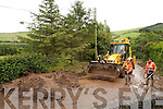 Council road staff Stephen Galvin and Tim Falvey clearing the roadway of mud. .Clearing the mudslide. ..
