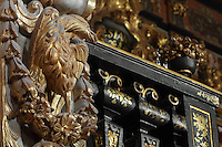 Detail of the bookcases with Chinese motifs, lacquer and gilding by Manuel da Silva, in the Black Room, and of a gilded bird and garland from the archway between the Black and Red rooms, in the Joanina Library, or Biblioteca Joanina, a Baroque library built 1717-28 by Gaspar Ferreira, part of the University of Coimbra General Library, in Coimbra, Portugal. The Casa da Livraria was built during the reign of King John V or Joao V, and consists of the Green Room, Red Room and Black Room, with 250,000 books dating from the 16th - 18th centuries. The library is part of the Faculty of Law and the University is housed in the buildings of the Royal Palace of Coimbra. The building is classified as a national monument and UNESCO World Heritage Site. Picture by Manuel Cohen