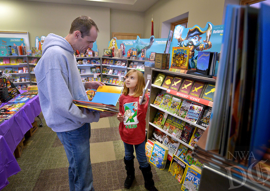 STAFF PHOTO BEN GOFF  @NWABenGoff -- 12/11/14 Jason Collins and daughter Gwyneth Collins, 7, of Bentonville look for books for Christmas presents and homeschool study during the Holiday Scholastic Book Fair at the Bentonville Public Library on Thursday Dec. 11, 2014. The Friends of the Bentonville Library exceeded their goal of $2,000 during the week-long sale, which will allow the library to add $1,000 worth of books from Scholastic to their collection.