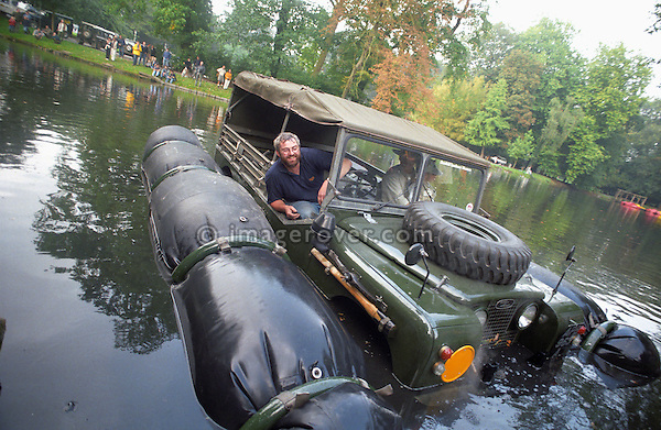 Phil Bashall swimming a historic 1963 APGP amphibious Land Rover with flotation bags in a lake to commemorate Land Rovers 50th anniversary at the 1998 Belgium National show.  RELEASES MAY BE AVAILABLE FOR CERTAIN USES, PLEASE ENQUIRE. Automotive trademarks are the property of the trademark holder, authorization may be needed for some uses. --- Info: This Land Rover is known as the A.P.G.P. , Air Portable General Purpose. Based around a 1 Ton military spec 109 24 Volt, it has amphibious capabilities. This LR floats! A small propeller is mounted on te rear propshaft, the air bags were inflated from the exhaust. This was to be a multi role vehicle. The APGP can be a radio station, wombat carrier or 110 Volt power tool source and could be stacked two high for air transport. About 26 of these vehicles were built for troop trials in 1964 but never entered service. This is the first vehicle to find its way into the Dunsfold Collection, purchased by Brian Bashall in 1968 via Ruddington military auctions. In 1998 for the 50th Anniversary of Land Rover Brians son, Philipp Bashall, had the mad idea to swim the APGP, which turned out to be an interesting challange as the flotation bags were by then already over 30 years old. Steering in the water is interesting as it relies on the front tyres as rudders, wind could be disastrous.