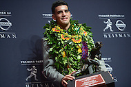 New York, NY - December 13, 2014: Hawaiian born Marcus Mariota, representing the Univeristy of Oregon, poses with the Heisman Memorial trophy at the New York Marriott Marquis after winning the prestigious award, December 13, 2014. Mariota held a passing efficiency of 186.3, completing 254 of his 372 passes for 3,783 yards and 38 touchdowns.  (Photo by Don Baxter/Media Images International)