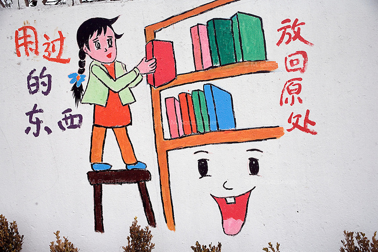 Murals depicting students and children doing homework and chores decorate the walls surrounding an elementary school in Pukou, Jiangsu, China.