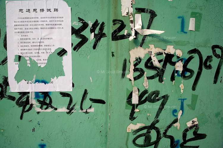 Day laborers phone numbers are painted on a wall in Pingliang, Gansu, China.