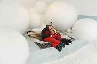 Sweden, SWE, Kiruna, 2006-Apr-12: A woman and a four years old girl sitting on a bed in a bedroom of the Jukkasjarvi icehotel.