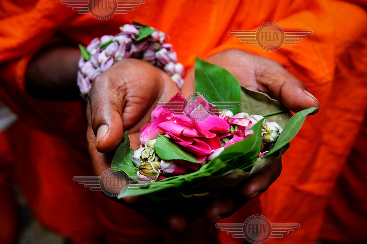 A devotee holds an offering of flower petals.