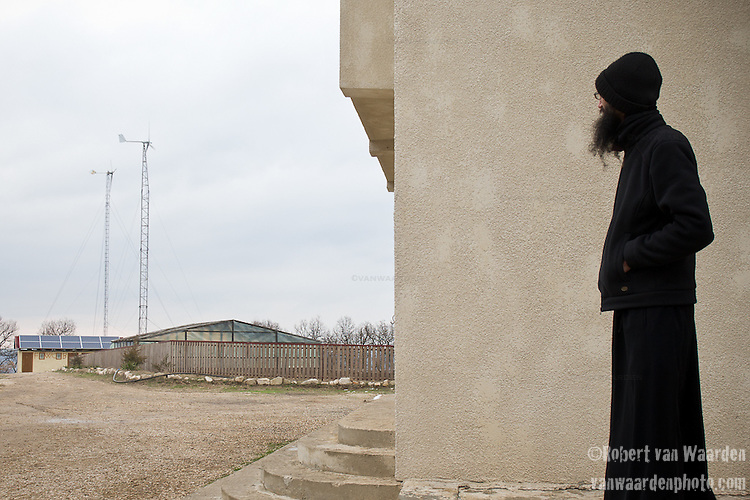 A monk at the Casian Monastery in Romania looks at the two wind turbines that are installed as part of the renewable energy system.
