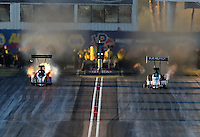 Feb. 22, 2013; Chandler, AZ, USA; NHRA top fuel dragster driver Mike Strasburg (left) has an engine fire racing alongside Brandon Bernstein during qualifying for the Arizona Nationals at Firebird International Raceway. Mandatory Credit: Mark J. Rebilas-