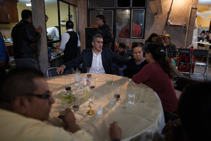 """Donovan sits with his wife and relatives at the wedding party of his sister-in-law in Iztapalapa, Mexico on October 31, 2015. Donovan Tavera, 43, is the director of """"Limpieza Forense México"""", the country's first and so far the only government-accredited forensic cleaning company. Since 2000, Tavera, a self-taught forensic technician, and his family have offered services to clean up homicides, unattended death, suicides, the homes of compulsive hoarders and houses destroyed by fire or flooding. Despite rising violence that has left 70,000 people dead and 23,000 disappeared since 2006, Mexico has only one certified forensic cleaner. As a consequence, the biological hazards associated with crime scenes are going unchecked all around the country. Photo by Bénédicte Desrus"""