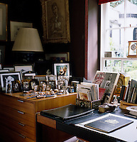 Detail of Lord Snowdon's desk and a plan chest covered in framed family photographs in his studio