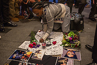 NEW YORK APRIL 21: A woman from the neihgborhood signing on aT-shirt at a makeshift memorial place created outside Apollo Theatre in Harlem, New York City, Friday, April 21, 2016. The pop star die a few hours ago at the age of 57.Photo by VIEWpress/Maite H. Mateo