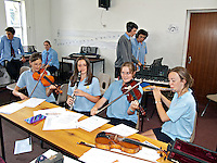 Schoolchildren learning to play the violin and musical instruments during a music lesson. This image may only be used to portray the subject in a positive manner..©shoutpictures.com..john@shoutpictures.com