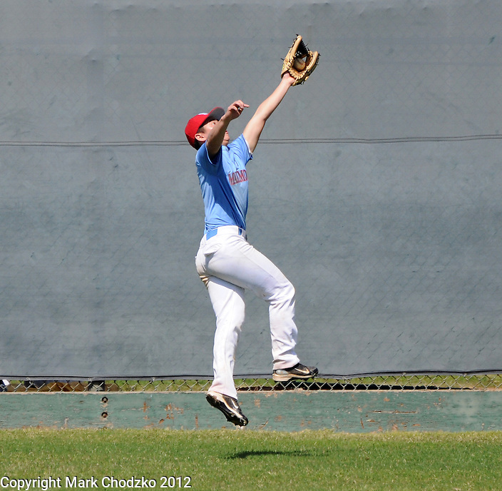 Baseball player makes a leaping catch in the outfield.