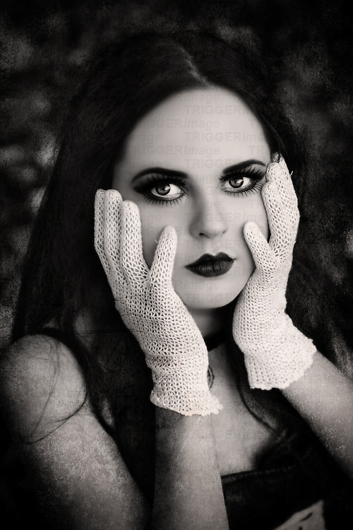 A close-up of a pretty girl with black hair, pale skin and heavy make-up,holding her face with hands in white gloves and looking at the camera.