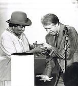 "United States President Jimmy Carter, right, reaches for the medal he dropped at a ceremony honoring famed soprano Marian Anderson, left, in the East Room of the White House in Washington, DC where Ms. Anderson was awarded the Congressional Gold Medal, the highest civilian honor bestowed by the United States Congress, for her work in promoting the Arts around the world on Thursday, October 17, 1987.  The President praised Anderson as one who has brought great joy to the nation.<br /> Credit: Benjamin E. ""Gene"" Forte / CNP"
