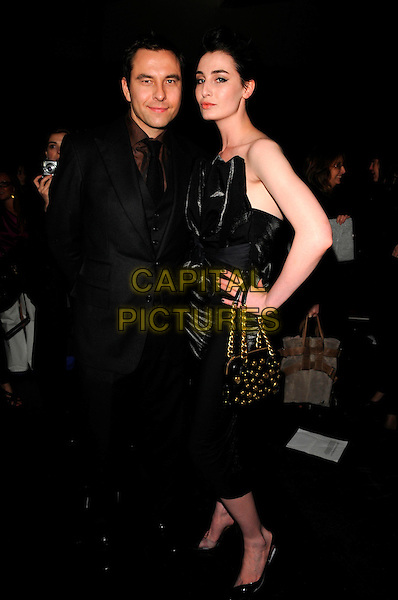 DAVID WALLIAMS & ERIN O'CONNOR.The Vivienne Westwood Red Label LFW catwalk show, The Old Sorting Post Office, New Oxford Street, London, England..February 14th, 2008.fashion week full length black strapless dress quilted gold chain bag purse suit hand on hip .CAP/CAN.©Can Nguyen/Capital Pictures.