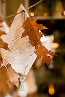 Printed pages from a book and  a collection of glass ornaments have been used to decorate a tree branch