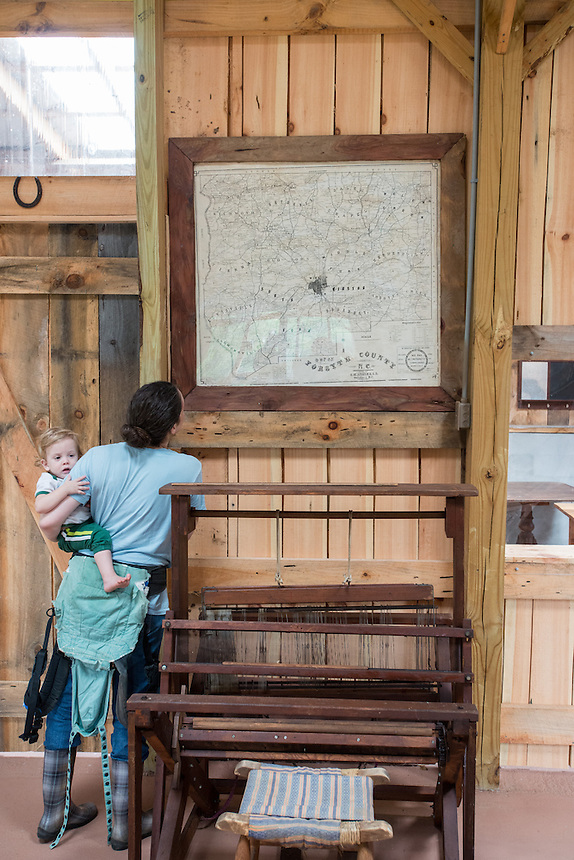 Wayne and Riely Woosley, retired school teachers, together with daughter J'nie Woosley (sic), give tours of their century old working farm. <br /> Mandie Rose  of Lewisville, NC holds 1-year-old Garet Engle (sic), as she looks at a map of Forsyth County dated 1902 that is one of the many historical artifacts on display at the farm. <br /> Woosley Farm, Pfafftown, NC. August 23, 2014.