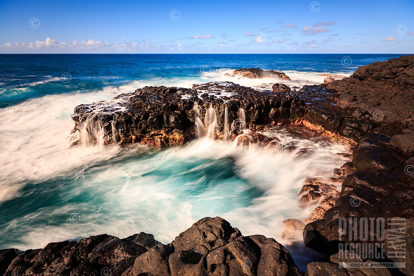 A dynamic ocean scene at Queen's Bath in Princeville, Kaua'i, depicts water flow in lines of white and pools of blue.
