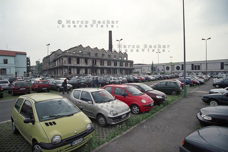 """Milano, quartiere Bovisa, periferia nord. Vecchia fabbrica di saponi """"Sirio"""" in disuso (ora demolita) davanti al parcheggio presso la stazione ferroviaria --- Milan, Bovisa district, north periphery. Old unused soap factory """"Sirio"""" (now demolished) in front of the parking at the railway station"""
