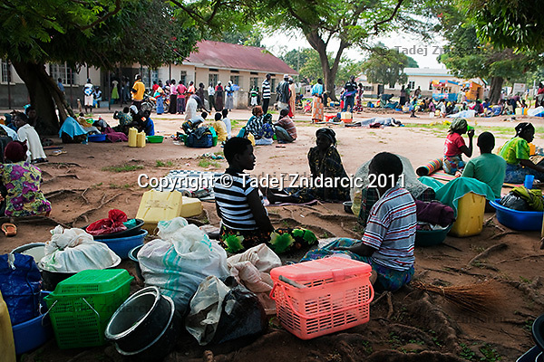 Relatives of expecting mothers wait outside the maternity ward of Arua Hospital, Uganda. Because the ward is not big enough to accommodate everyone they are not allowed inside.