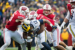 Wisconsin Badgers linebackers Ryan Connelly (43), T.J. Edwards (53) and Andrew Van Ginkel (17) tackle running back Chris Evans (12) during an NCAA College Big Ten Conference football game against the Michigan Wolverines Saturday, November 18, 2017, in Madison, Wis. The Badgers won 24-10. (Photo by David Stluka)