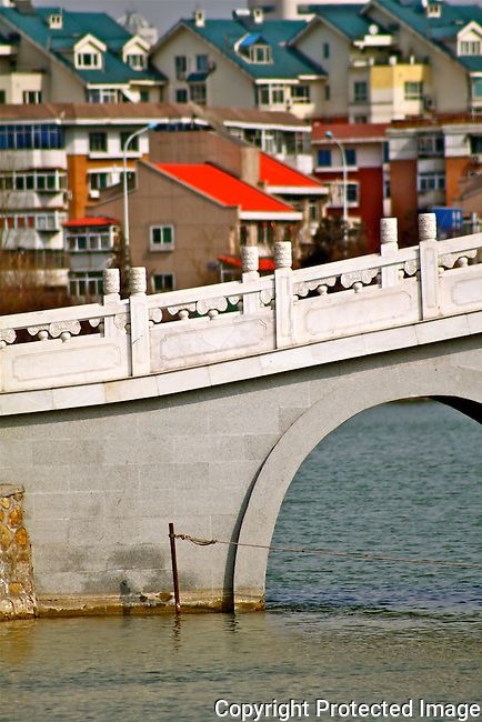Local housing by water front white chinese stone bridge with arch photo