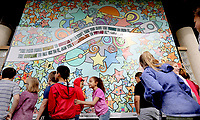 NWA Democrat-Gazette/DAVID GOTTSCHALK Students with Lee Elementary School stand Friday, May 10, 2019, with their newly unveiled mural 12 x 14 foot mural on permanent display at the city of Springdale Aquatic Center at Murphy Park. Lee Elementary School in partnership with Art Feeds created the mural with students from Springdale High School and Tyson Middle School.Funding by the Walmart Foundation made the mural possible.