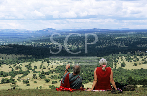 Olenkapune, Kenya. Middleaged white tourist couple resting on a hillside overlooking the Rift Valley in the Maasai Mara reserve.