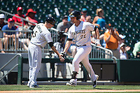 Matt Davidson (22) of the Charlotte Knights slaps hands with third base coach Ryan Newman (5) as he rounds the bases after hitting a home run against the Indianapolis Indians at BB&T BallPark on June 21, 2015 in Charlotte, North Carolina.  The Knights defeated the Indians 13-1.  (Brian Westerholt/Four Seam Images)