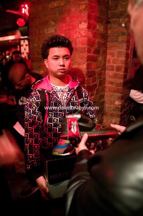 A seller and a buyer discuss a pair of sneakers during Dunkxchange, a market held in a club in New York City, USA, where sneaker collectors trade and sell their rare shoes, 7 January 2007.<br />