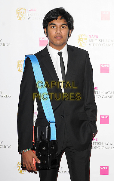 HIMESH PATEL .The Game BAFTA Video Game Awards, Hilton Hotel, Park Lane, London, England, UK, 16th March 2011..half length black suit tie blue strap bag .CAP/CAN.©Can Nguyen/Capital Pictures.