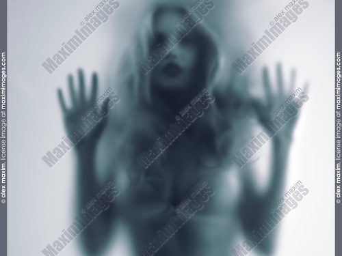 Dramatic expressive concept of a blurred sensual young woman ghost-like silhouette behind a hazy frosted glass