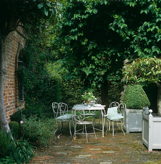 A pretty white wrought-iron garden table and chairs are placed in a patch of sunlight on a brick patio in the garden