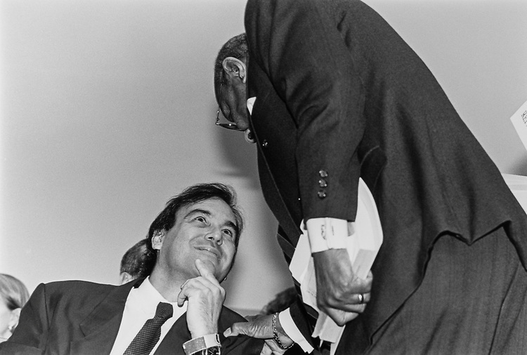 Rep. Louis Stokes, D-Ohio, stoops over to greet Oliver Stone at House Government Operations Committee hearing on April 30, 1992. (Photo by Laura Patterson/CQ Roll Call)