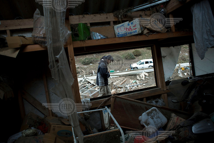 A woman sifts through the debris at her home where two family members were killed. Thousands of people died in this small town which ran out of body bags. On 11 March 2011 a magnitude 9 earthquake struck 130 km off the coast of Northern Japan causing a massive Tsunami that swept across the coast of Northern Honshu. The earthquake and tsunami caused extensive damage and loss of life.