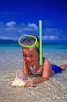 Boy wearing mask and snorkel in water at beach with shell