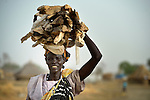 A displaced woman carries firewood home in Agok, a town in the contested Abyei region where tens of thousands of people fled in 2011 after an attack by soldiers and militias from the northern Republic of Sudan on most parts of Abyei. Although the 2005 Comprehensive Peace Agreement called for residents of Abyei--which sits on the border between Sudan and South Sudan--to hold a referendum on whether they wanted to align with the north or the newly independent South Sudan, the government in Khartoum and northern-backed Misseriya nomads, excluded from voting as they only live part of the year in Abyei, blocked the vote and attacked the majority Dinka Ngok population. The African Union has proposed a new peace plan, including a referendum to be held in October 2013, but it has been rejected by the Misseriya and Khartoum. The Catholic parish of Abyei, with support from Caritas South Sudan and other international church partners, has maintained its pastoral presence among the displaced and assisted them with food, shelter, and other relief supplies.