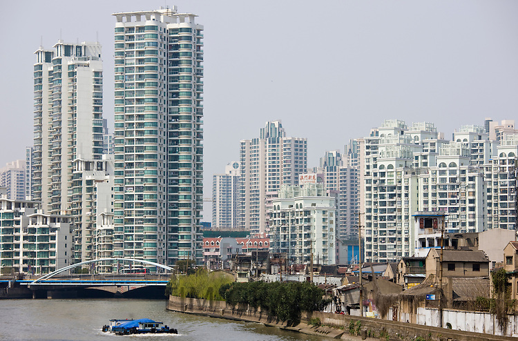 Traditional houses in the shadow of new high rise apartment blocks in city centre, Shanghai, China