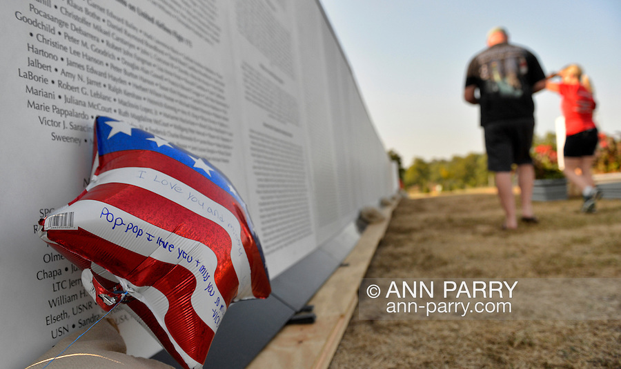 """East Meadow, New York, U.S. 11th September 2013. A patriotic red white and blue balloon has messages written on it to William V. Steckman (Pop-Pop) of West Hempstead, who worked in the North Tower of Twin Towers, and died 9/11 2001. A man and woman were walking along the Global War on Terror """"Wall of Remembrance"""" a traveling memorial on display in New York for the first time, at Eisenhower Park on the 12th Anniversary of the terrorist attacks of 9/11. The unique 94 feet long by 6 feet high wall has, on one side, almost 11,000 names of those lost on September 11th 2001, along with heroes and veterans who lost their lives defending freedom of Americans over past 30 years."""