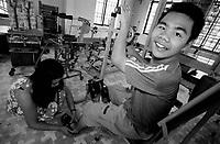 Kontum / Vietnam.<br /> Centro per l'assistenza e la cura delle vittime dell'agent orange.<br /> Tran Hai Phong ha 14 anni ed è nato come centinaia di bambini del distretto di Kontum con gravi menomazioni a causa delle mutazioni genetiche causate dall'agent orange.Grazie alle terapie ha compiuto notevoli progressi e adesso riesce a camminare da solo appoggiandosi ad un bastone.Nella fotografia il giovane Tran mentre compie i suoi quotidiani esercizi di fisioterapia con l'aiuto della madre Nguyen Thi Hanh di 39 anni.<br /> Foto Livio Senigalliesi.<br /> Kontum / Vietnam.Centre for victims of dioxine syndrome.Tran Hai Phong (14) during his everyday physical training.<br /> Photo Livio Senigalliesi