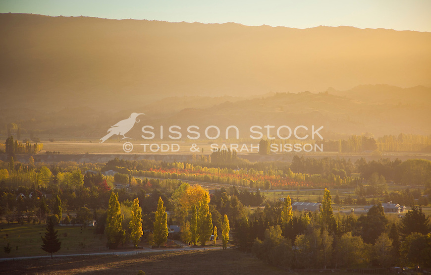 Soft hazy light illuminates the Clutha River Valley near Clyde at sunset on an  autumn evening in Central Otago, South Island, New Zealand