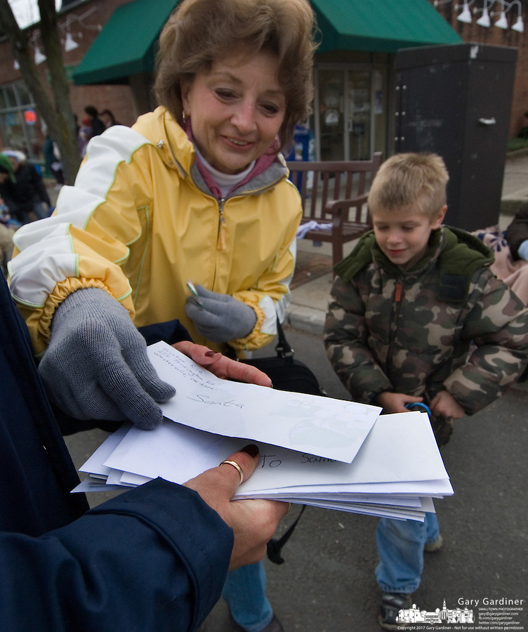 A woman and her son hand their letter toSanta to a postal worker walking the Christmas parade in Westerville, Ohio, Sunday, Dec. 3, 2006.<br />