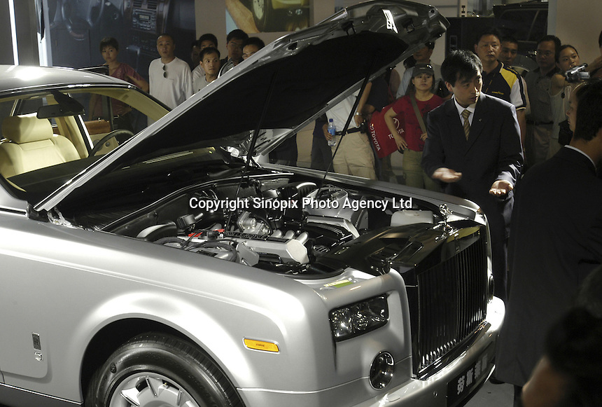 Visitors look at a Rolls-Royce car at the Auto China 2004 exhibition in Beijing, China. China's booming economy has led to rocketing car production and sales, with car makers from all over the world seeking a piece of the action..