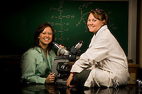 Two female college students in the biology lab with a microscope at a college in Belmont, NC.