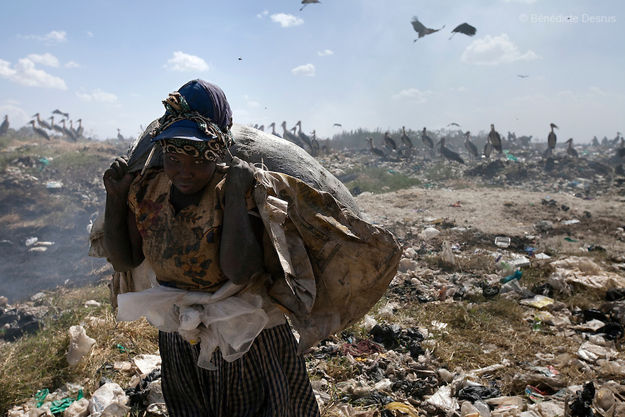 13 february 2013 - Dandora dumpsite, Nairobi, Kenya - A Kenyan woman lifts a sack of recyclable materials at the Dandora dumpsite, one of the largest and most toxic in Africa. Located near slums in the east of the Kenyan capital Nairobi, the open dump site was created in 1975 and covers 30 acres. The site receives 2,000 tonnes of unfiltered garbage daily, including hazardous chemical and hospital wastes. It is a source of survival for many people living in the surrounding slums, however it also harms children and adults' health in the area and pollutes the Kenyan capital. Photo credit: Benedicte Desrus