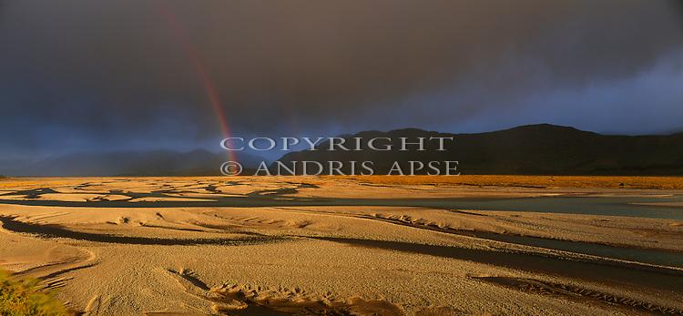 Rainbow over the Rakaia River. Canterbury Region.  New Zealand